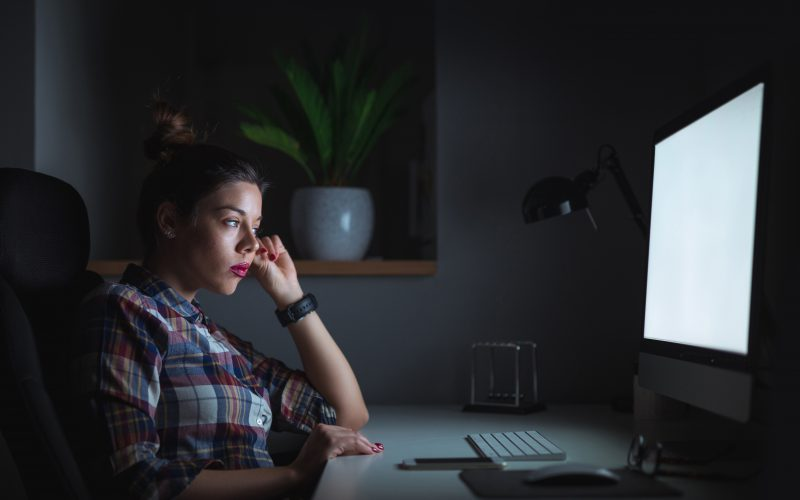 Woman working on a computer in the dark
