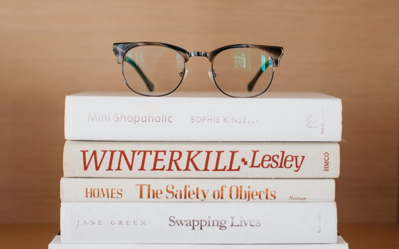 Kepler Browline Glasses in Tortoise on a stack of books