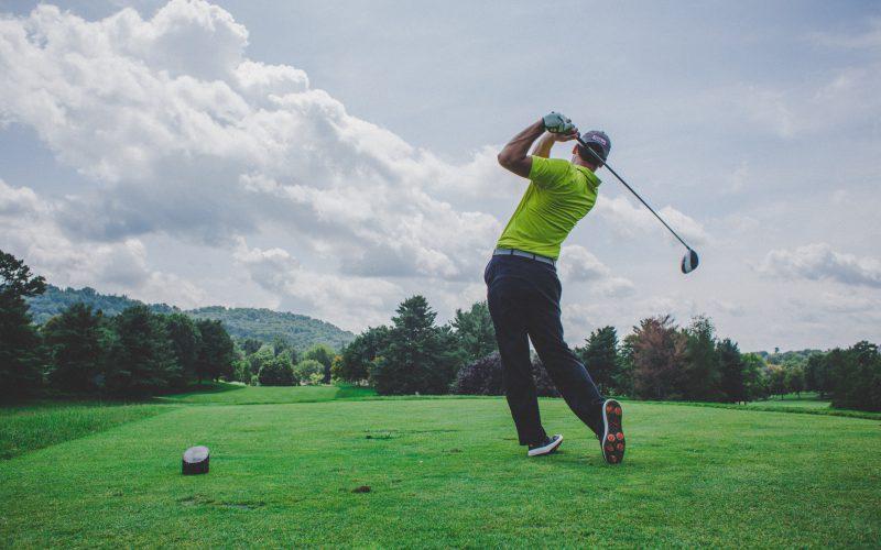 Man swinging a golf club on a golf course