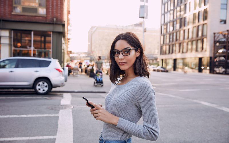 Woman crossing the street with phone wearing Felix Gray blue light glasses
