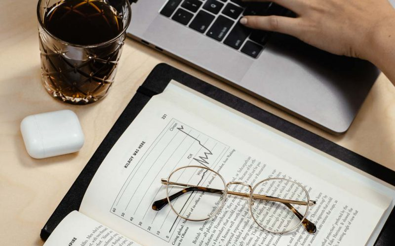 Glasses on a book next to someone typing on a laptop with a cup of coffee