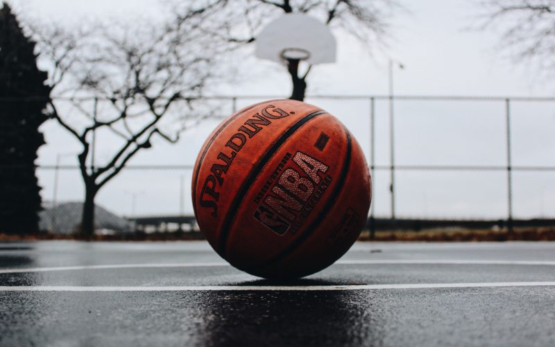 Basketball on a court with a hoop in the background