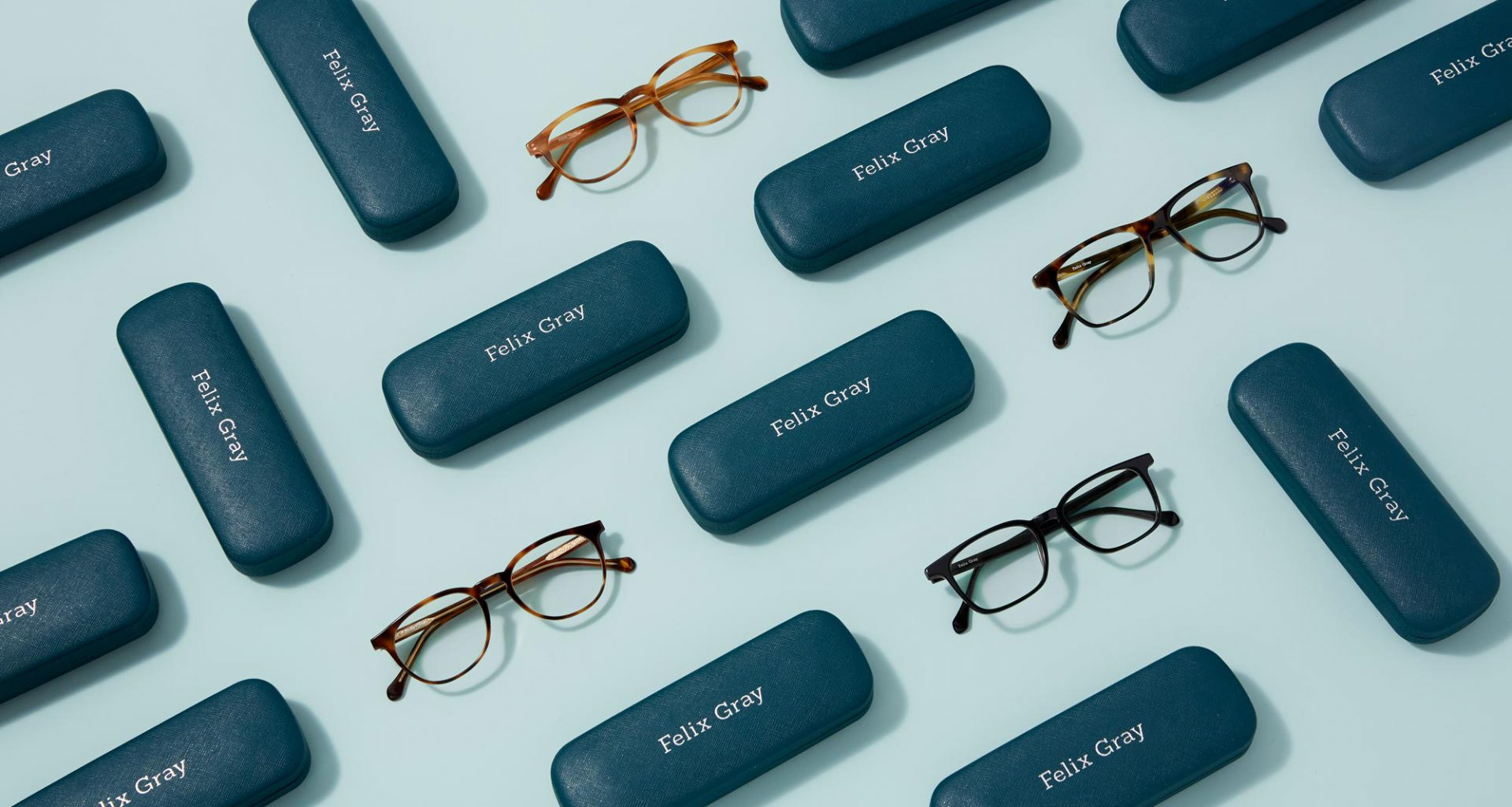A variety of eyeglasses and teal glasses cases on a blue background.