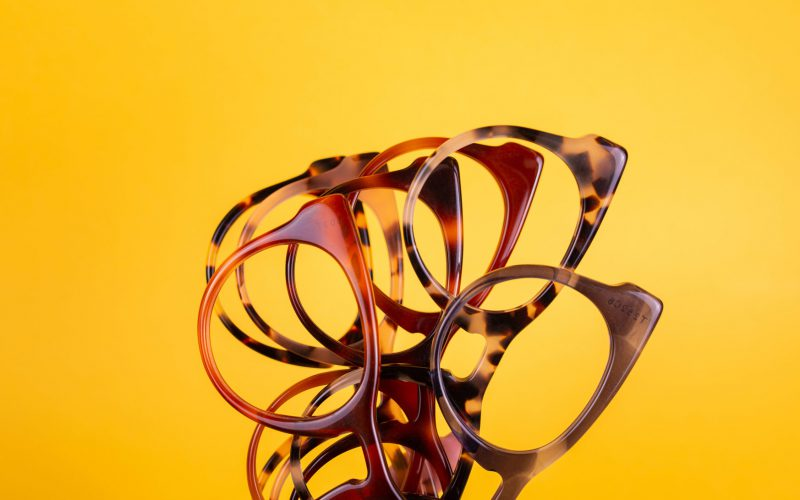 A variety of colorful acetate eyeglasses frames on a yellow background