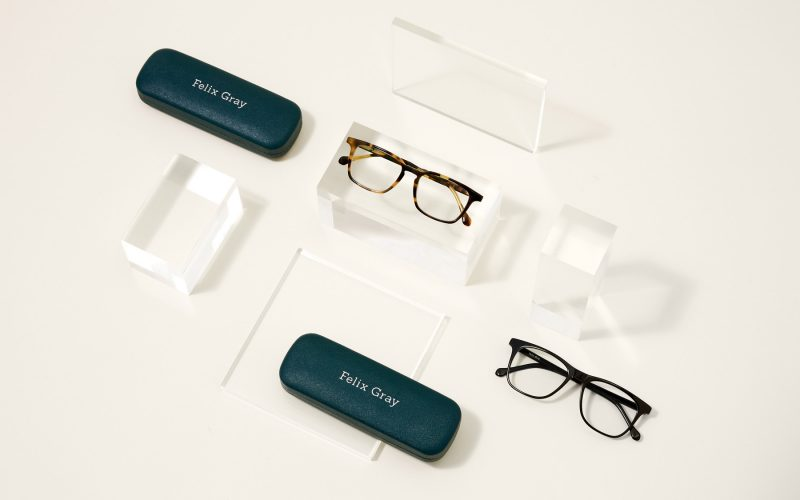 Two pairs of Felix Gray eyeglasses, two teal glasses cases and clear props
