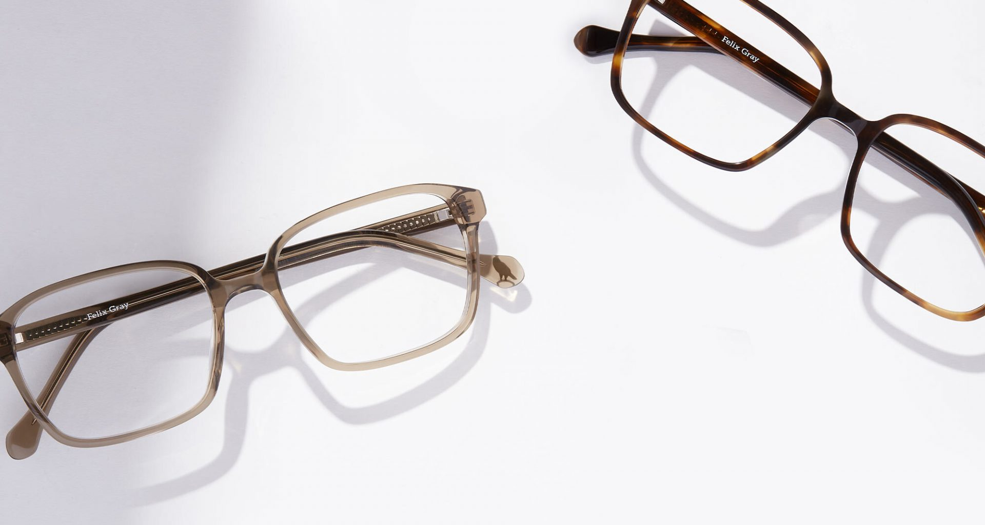 A pair of square soft champagne colored eyeglasses next to a pair of brown square eyeglasses