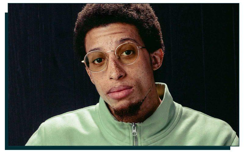 Man wearing gold eyeglasses and green sweater