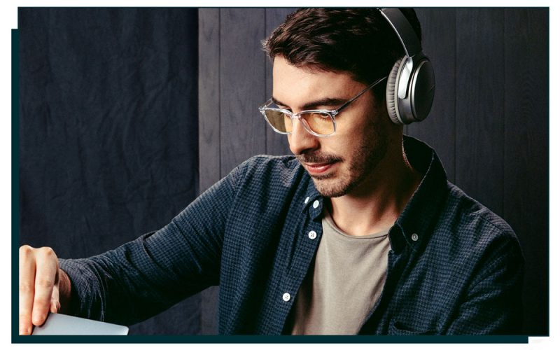 image of man wearing glasses and headphones looking towards a laptop