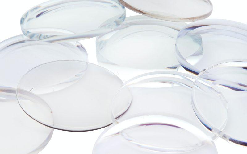 A pile of clear eyeglass lenses