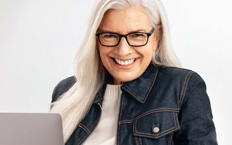 Woman wearing reading glasses and with laptop on her lap