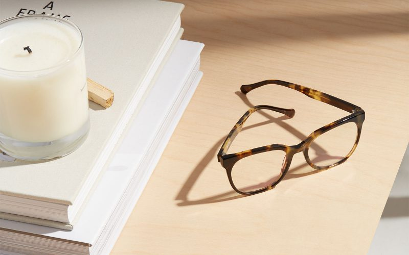 Image of brown eyeglasses next to a candle and book
